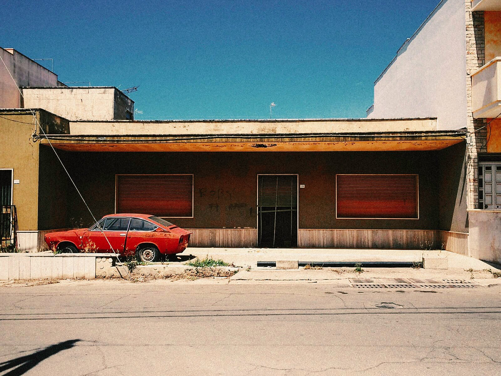 elisabetta riccio - urban vision- red car from the 30s abandoned in puglia in front of a house