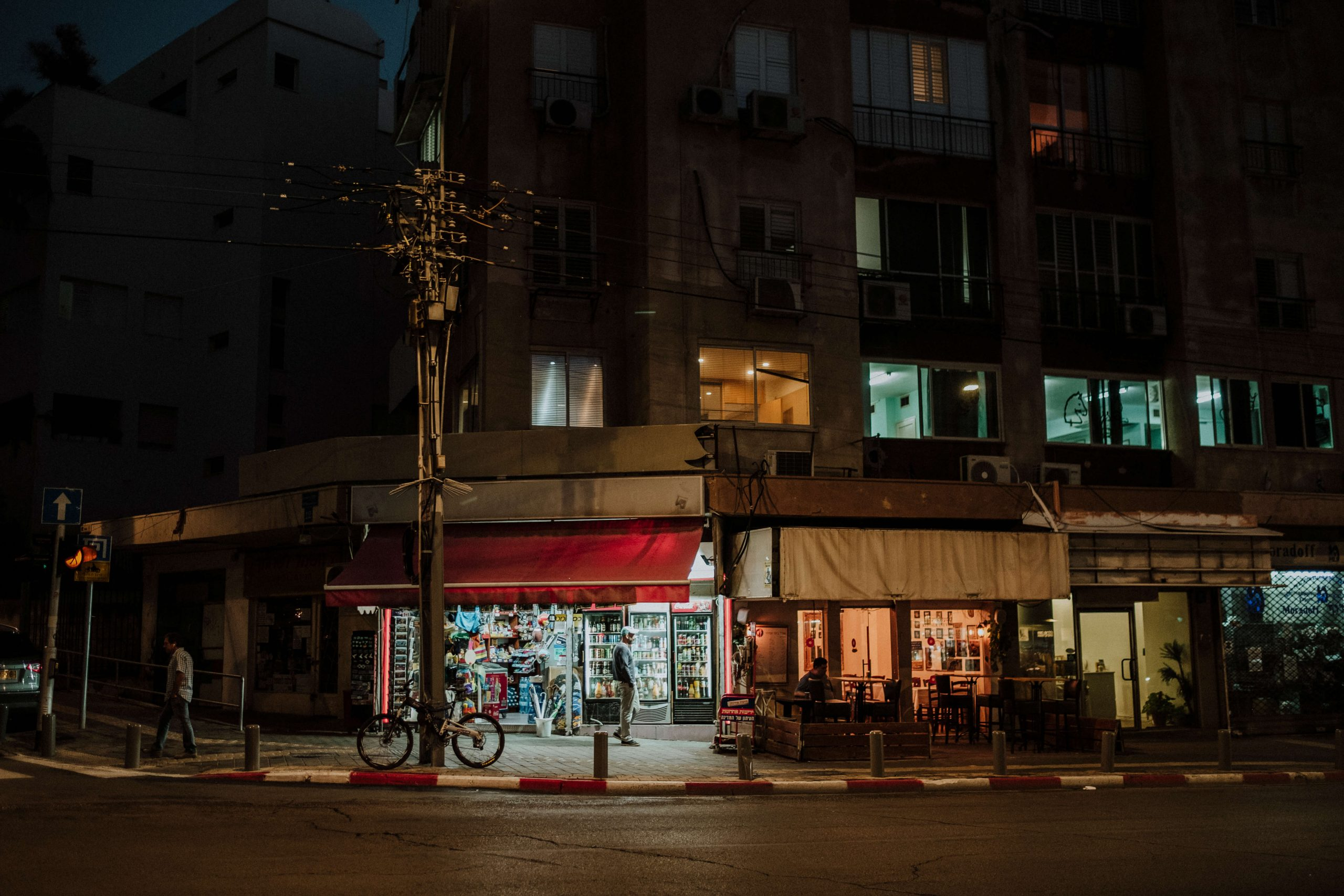 elisabetta riccio - urban vision - crossing a street illuminated by artificial light in Tel Aviv, a man is in front of a shop