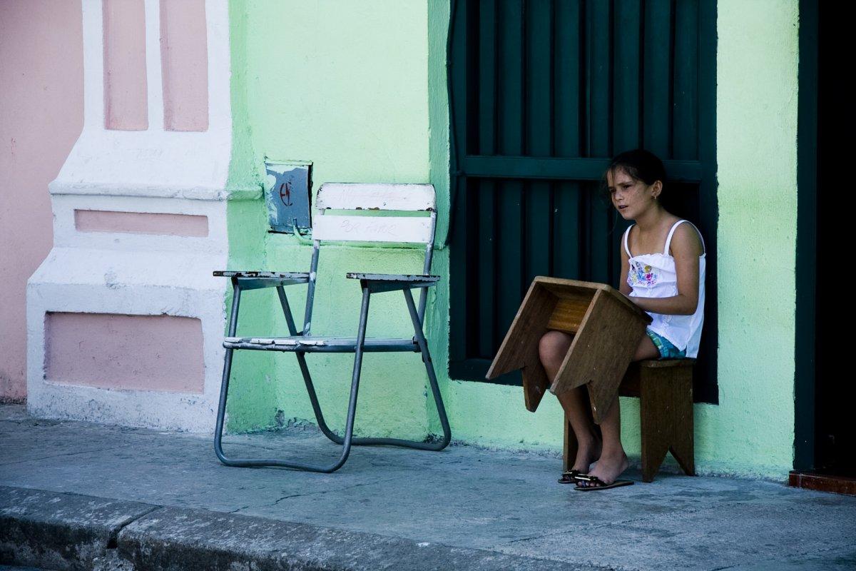 little girl sitting on a chair in a street of Havana