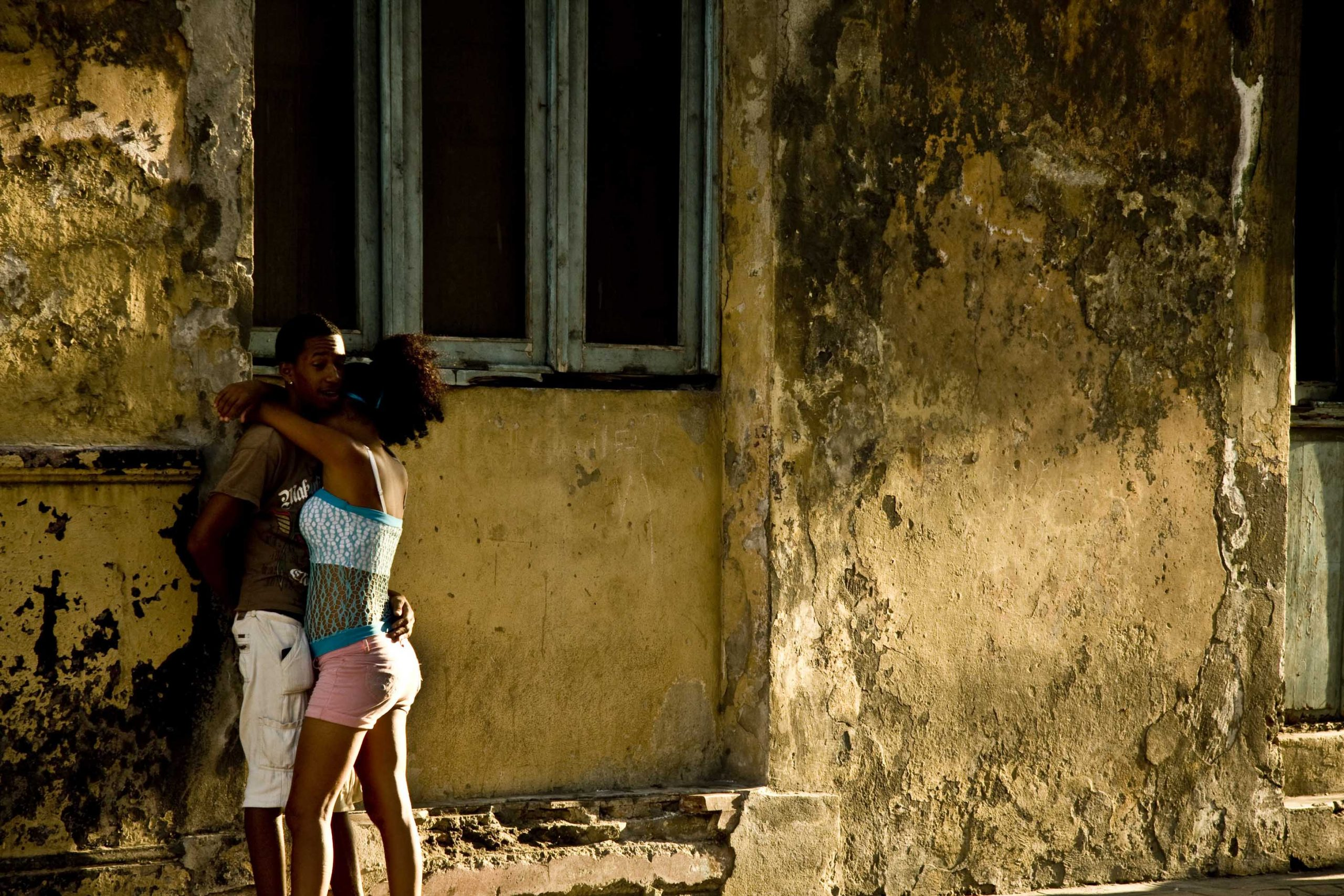 two young people embracing each other on the streets of cuba