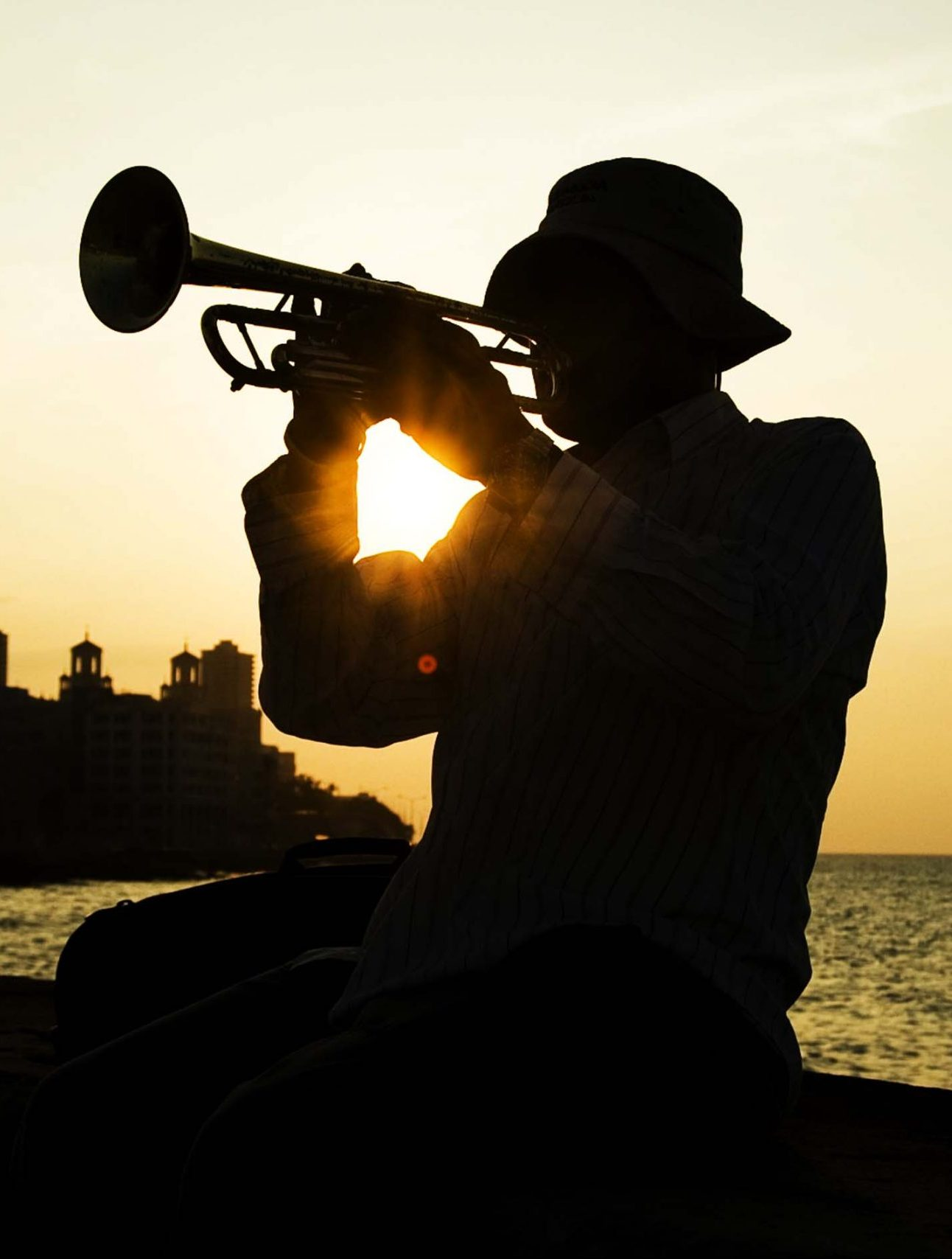 a man is playing trumpet while the sunrise in Havana